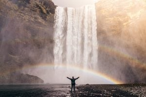 Photo of a man standing at the foot of a waterfall with a double rainbow with his arms outstretched.