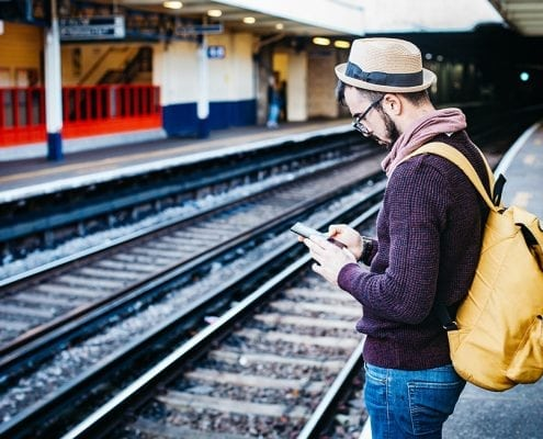 A photo of a man stood waiting for a train checking his phone