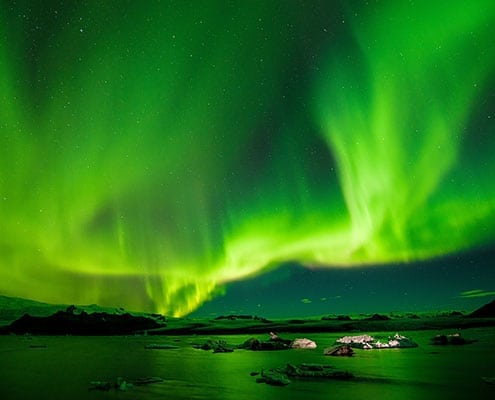 A photo of green northern lights in the sky above Iceland by Paul Morris